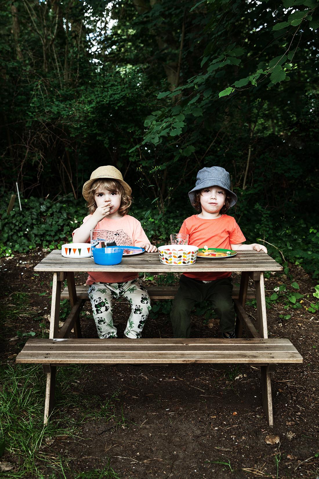 Zwei Jungen an Picknicktisch. Kinderportrait von der Kinderfotografin © Miriam Ellerbrake, Berlin